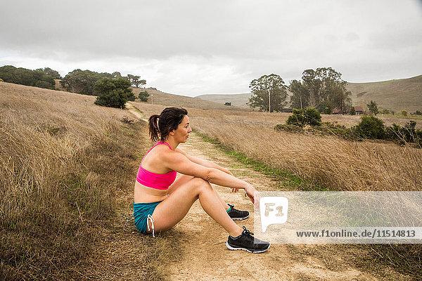 Weibliche Läuferin am Feldweg in der Landschaft