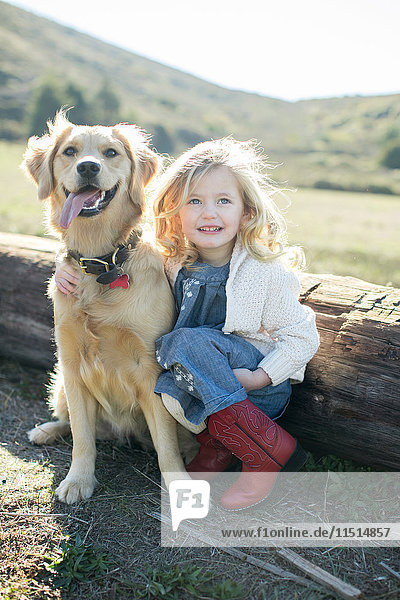 Portrait of girl and dog sitting by log