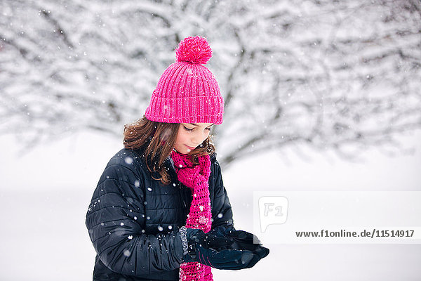 Girl cupping hands to catch falling snow