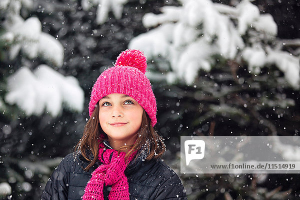 Girl in pink knitted hat looking up at falling snow