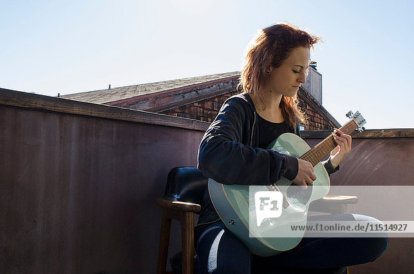 Teenager playing guitar on roof terrace