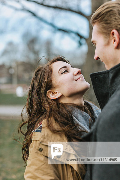 Young couple standing in park  face to face  smiling