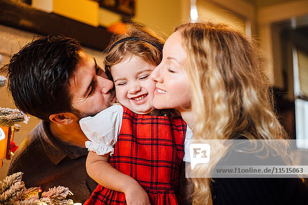Female toddler between parents kissing her on cheek at christmas