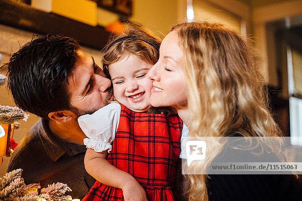 Weibliches Kleinkind zwischen Eltern  die es zu Weihnachten auf die Wange küssen