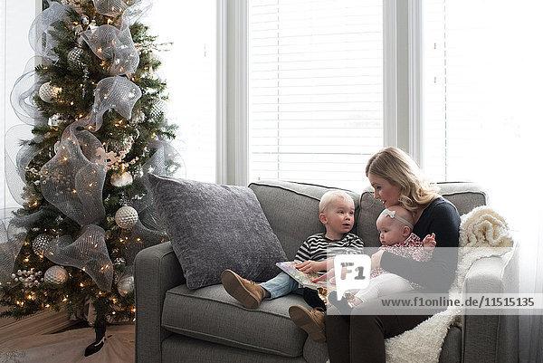 Mutter und Kinder sitzen auf dem Sofa und schauen sich das Buch an.