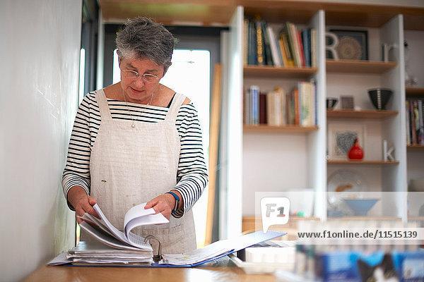 Ältere Frau in der Küche  die Akte durchsieht