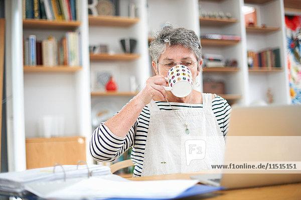 Ältere Frau zu Hause  benutzt Laptop  trinkt heißes Getränk