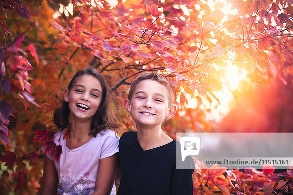 Portrait of boy and girl in rural setting at sunset  laughing