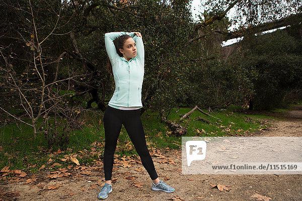 Junge Frau beim Sport  beim Stretching  im Freien