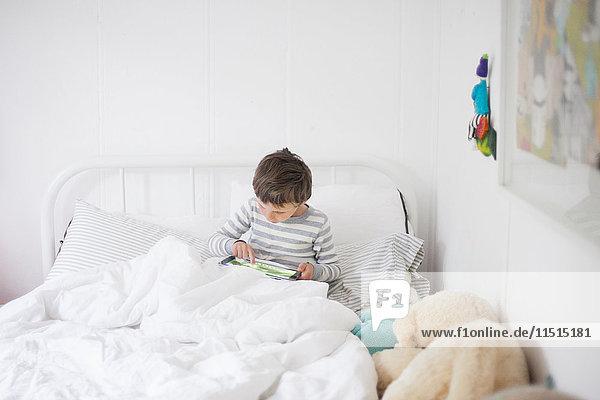 Aufrecht im Bett sitzender Junge spielt Videospiel auf digitalem Tablet