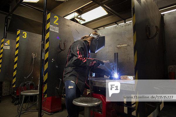 Schlosserin beim Schweißen von Metall an der Werkbank