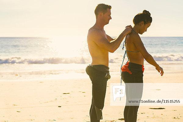Mann hilft Freundin beim Anziehen eines Neoprenanzugs in Newport Beach  Kalifornien  USA