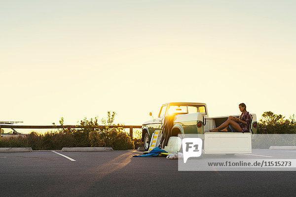 Junge Surferin betrachtet ein Smartphone auf dem Rücksitz eines Pickup-Trucks in Newport Beach  Kalifornien  USA