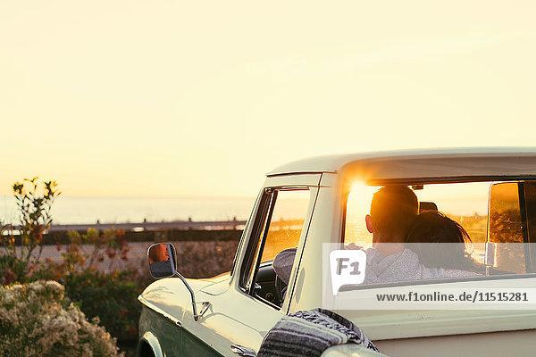 Rückansicht eines Paares in einem Kleintransporter beim Sonnenuntergang in Newport Beach  Kalifornien  USA