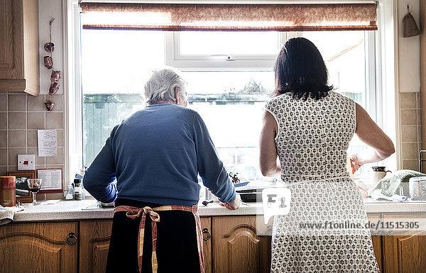 Mutter und erwachsene Tochter spülen gemeinsam Geschirr