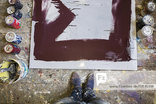 Legs of Mari man standing near paint cans and canvas on floor