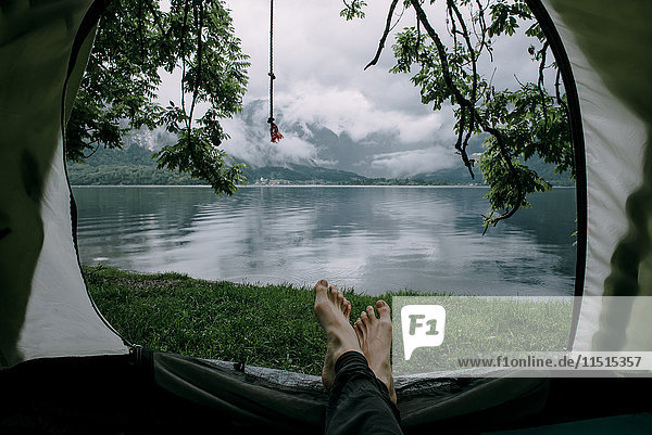Feet on man laying in camping tent at lake