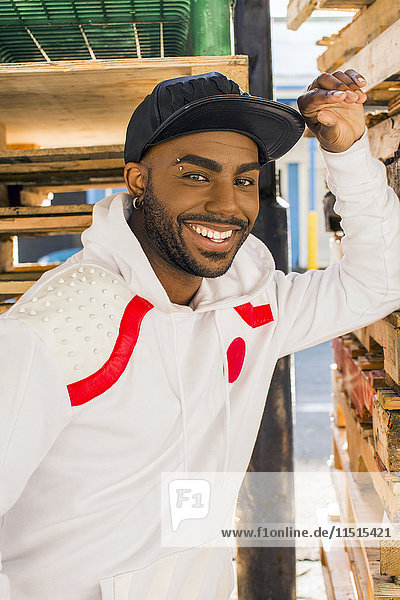 Smiling Black man leaning on wooden pallets