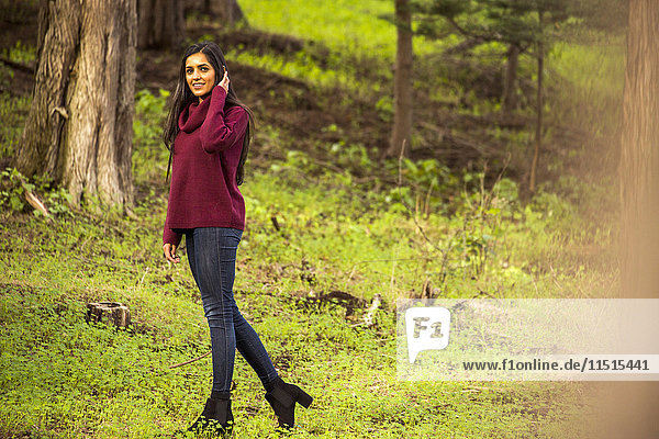 Smiling Indian woman posing in forest