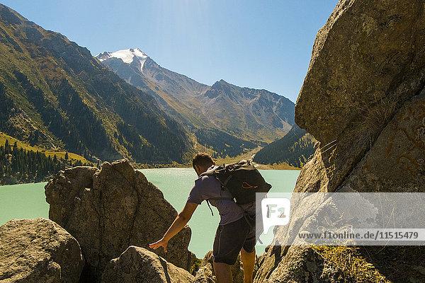 Caucasian man backpacking near mountain lake