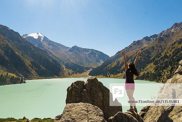 Caucasian woman celebrating on rocks near mountain lake