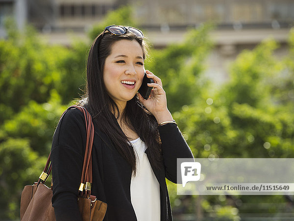 Chinese businesswoman talking on cell phone outdoors