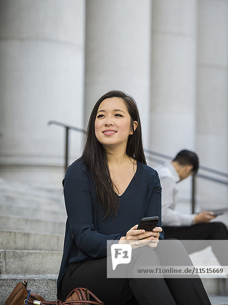 Chinese businesswoman sitting on staircase holding cell phone