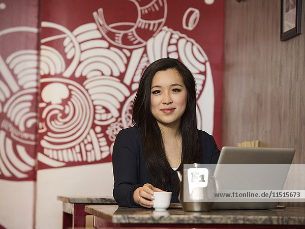 Chinese businesswoman drinking tea and using laptop