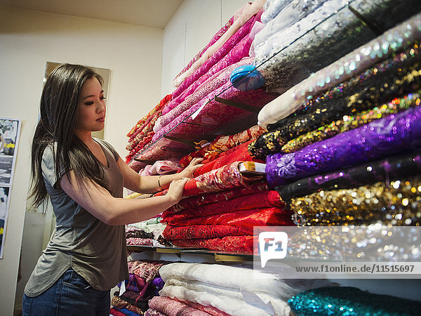 Chinese woman shopping for fabric in store