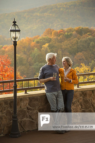 Older Caucasian couple enjoying wine and scenic view