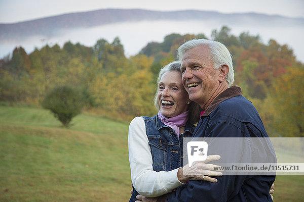 Older Caucasian couple hugging in field