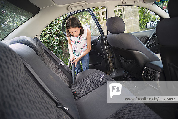 Mixed Race girl vacuuming car interior