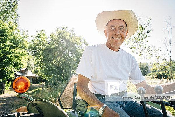 Caucasian farmer sitting on tractor
