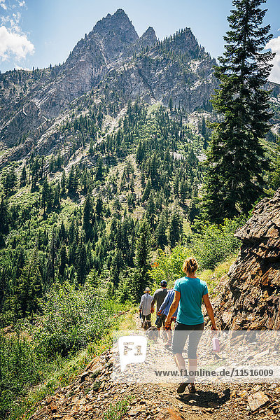 Caucasian people hiking on path in mountains