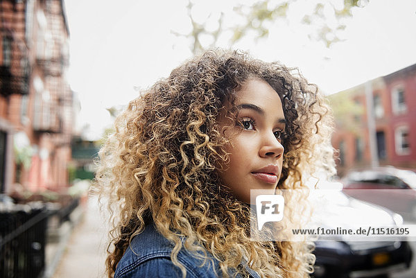 Pensive Mixed Race woman in city
