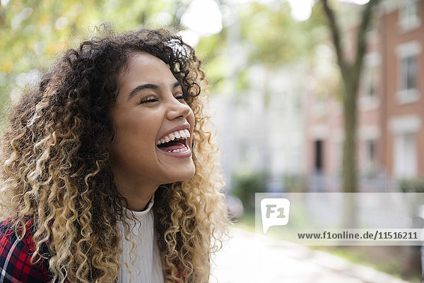 Mixed Race woman laughing in city