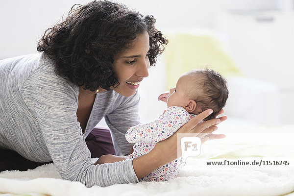 Hispanic mother laying on bed holding baby daughter