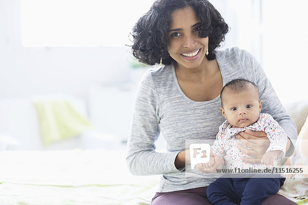 Hispanic mother posing with baby daughter