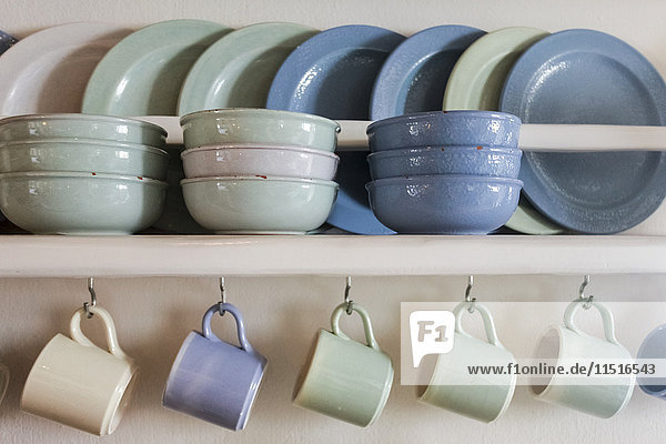 Blue and green plates  bowls and coffee cups on shelf