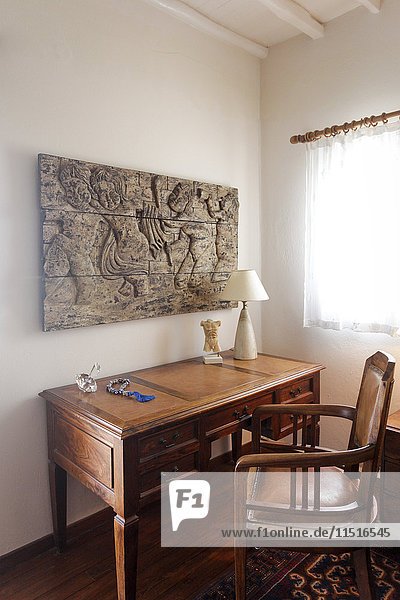 Sculpture on wall above desk and chair