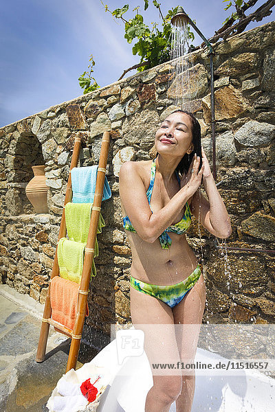 Woman wearing bikini under outdoor shower