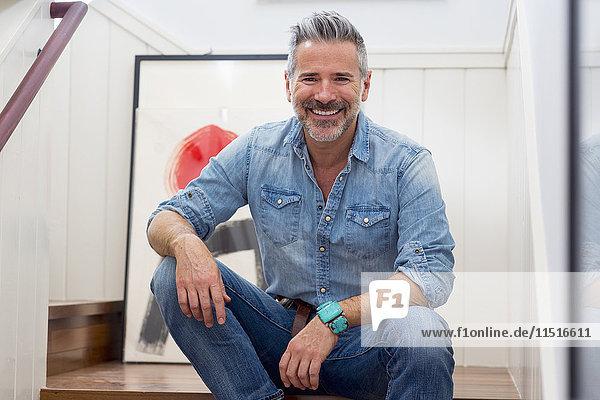Smiling Caucasian man sitting on staircase
