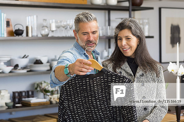 Man showing sweater to woman in store
