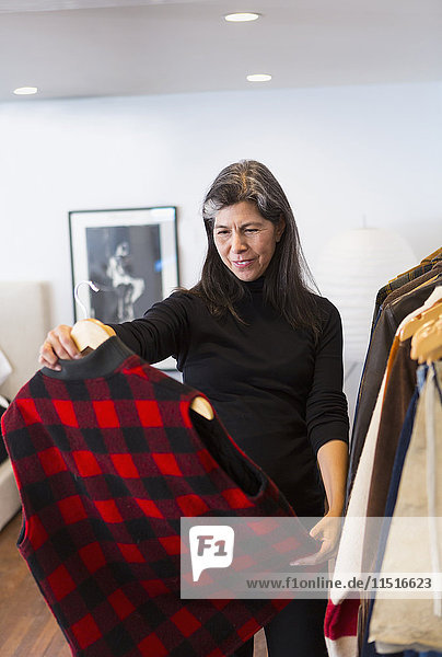 Hispanic woman examining plaid vest in store