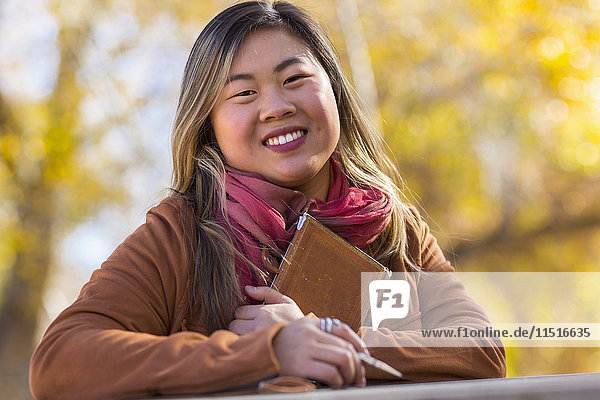 Portrait of smiling Asian woman in autumn
