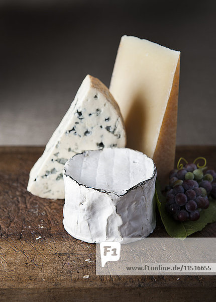 Artisanal cheese and grapes on wooden table