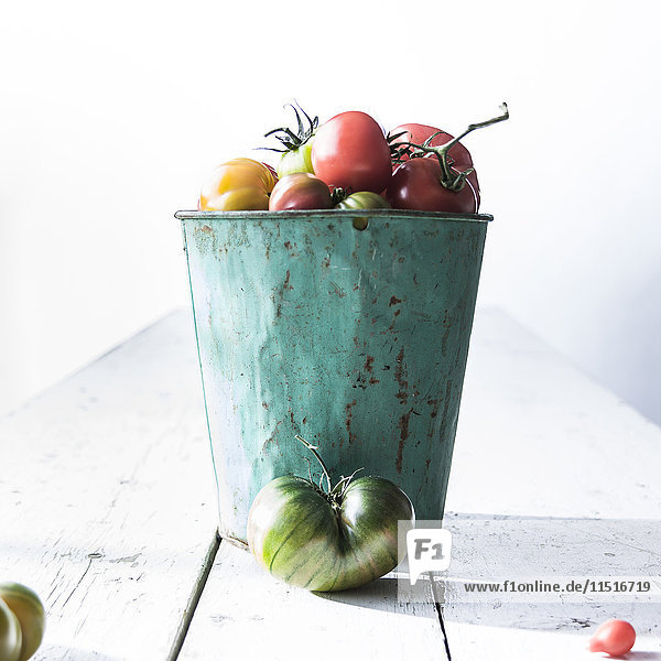 Bucket of fresh tomatoes on wooden table