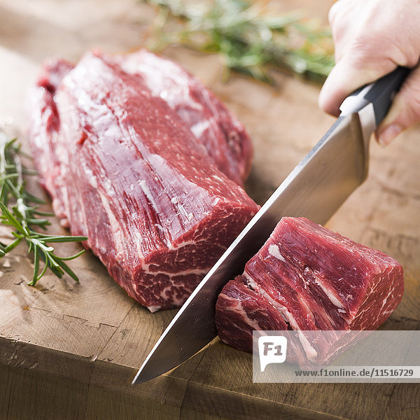 Knife cutting beef tenderloin on wooden table