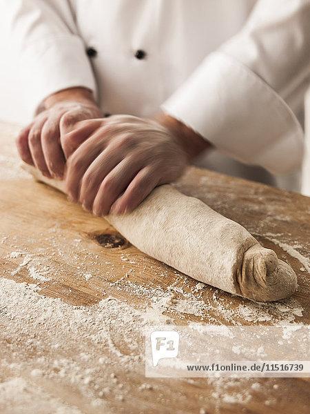 Hands of baker rolling dough