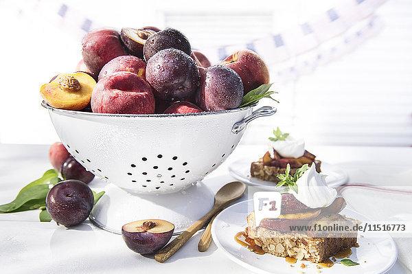 Bowl of fresh fruit in colander with dessert cake